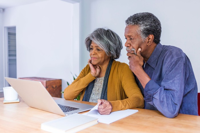 Older couple looking at laptop with concerned expressions.