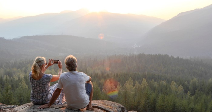 An older couple looking out over beautiful scenery from a mountain top.