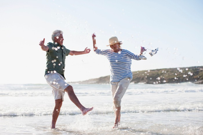 Seniors dancing in the surf at a beach.