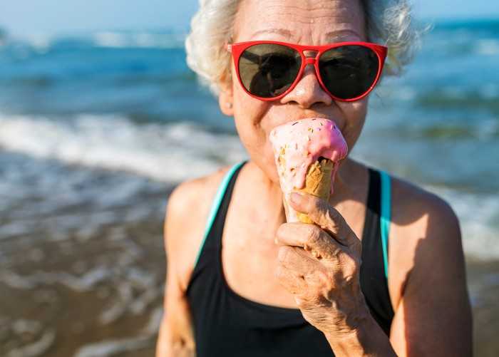 Senior woman in red sunglasses eating a strawberry ice cream cone.