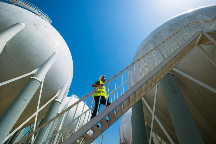 A man walking up a stairwell between multiple energy storage tanks.