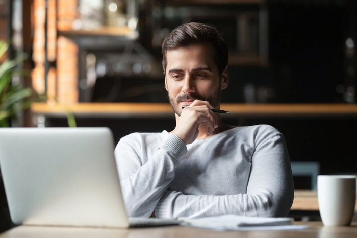 A young bearded man holding his chin looking at his laptop screen  at a table in a large office or shared work space.