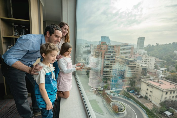 Excited family of four at their hotel bedroom looking at a beautiful window view all smiling