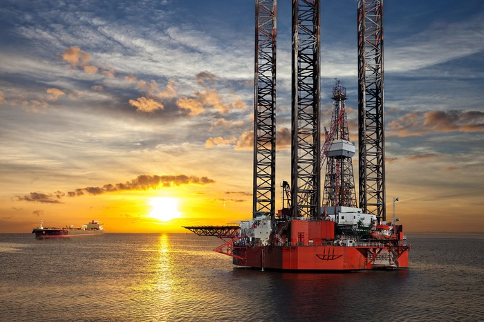 Oil platform and tanker ship in offshore area at sunset.