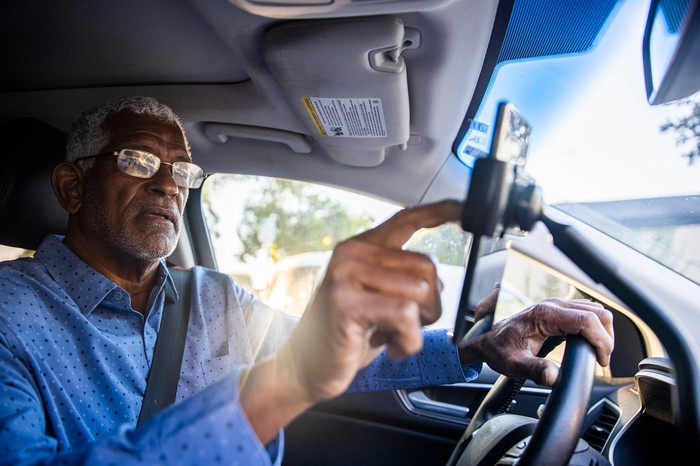 Senior gig worker using ride sharing app while in the driver's seat.