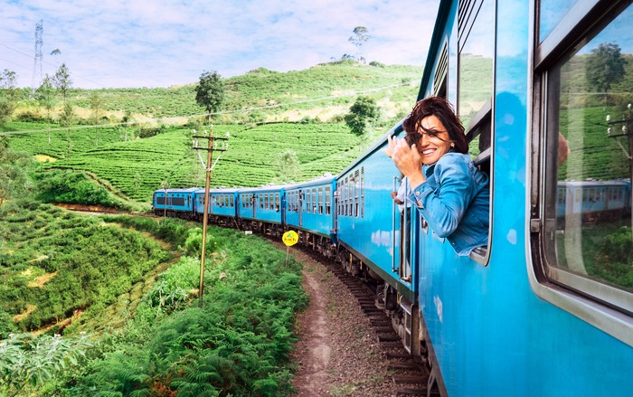 A woman looks out a train window at green countryside.