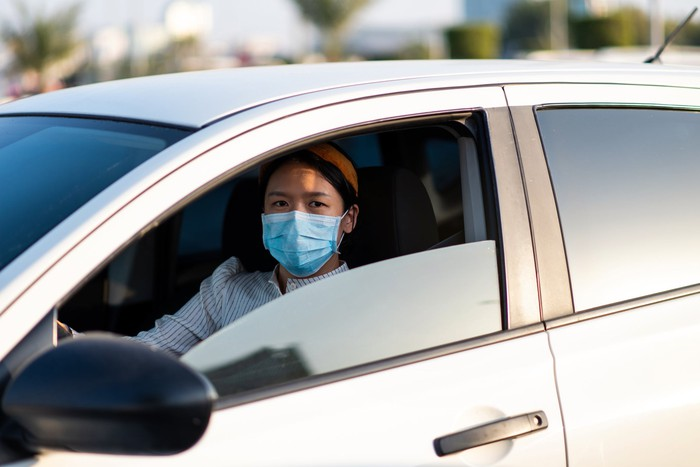 Woman in face mask driving a car.