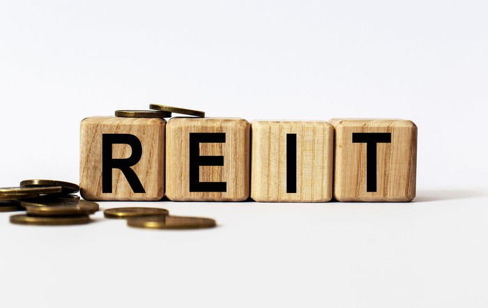 """""""REIT"""" spelled out in wooden blocks, and festooned with coins."""