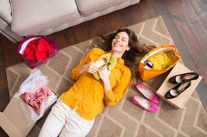 A shopper lying on the floor with new purchases of shoes and clothing.