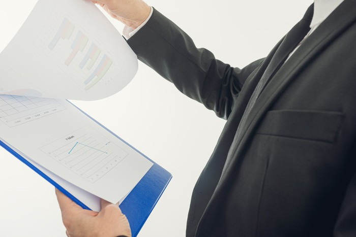 A man in a suit looking over paperwork on a clipboard.
