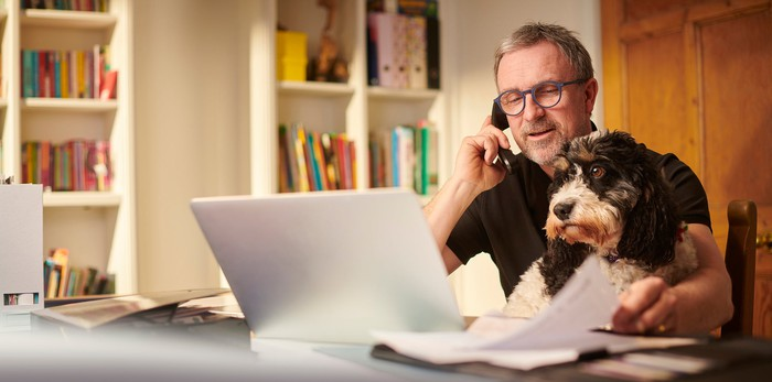 Man with dog on lap while looking at computer and talking on phone.
