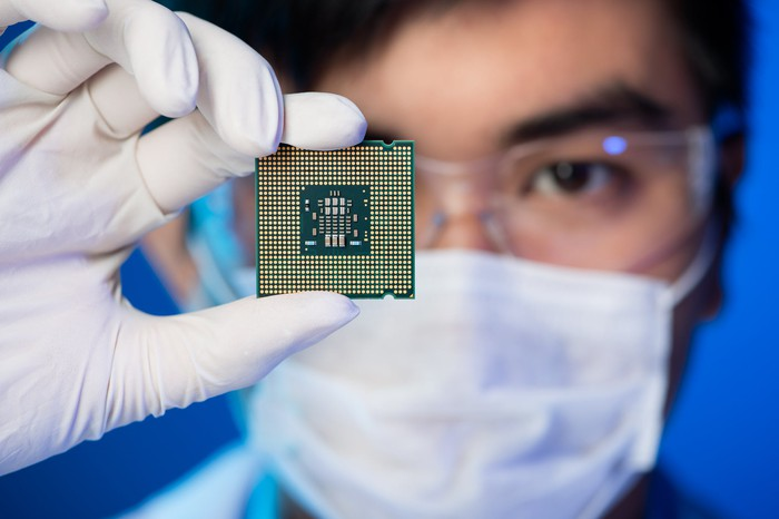 Person wearing mask and lab coat holding semiconductor chip in gloved hand.