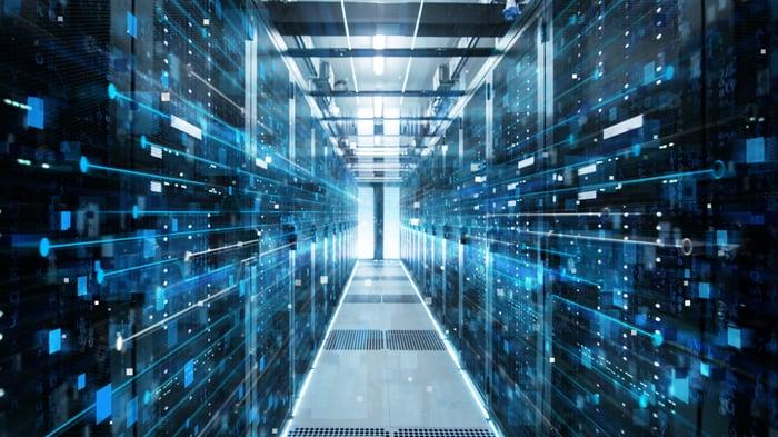 A corridor through two walls of servers in a data center.