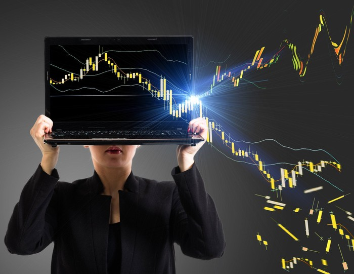 A businesswoman holding a laptop, with a stock chart coming out of the screen and heading both higher and lower.