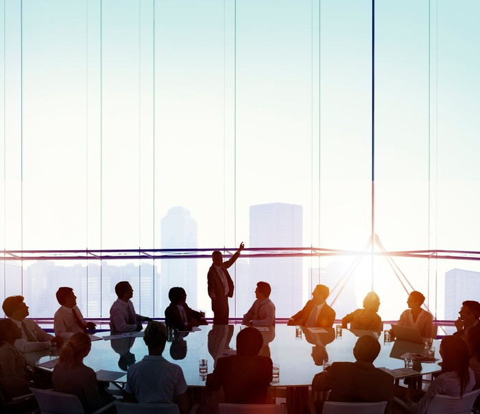People are sitting at a round table looking at a person who is standing with his hand pointing toward the sky.