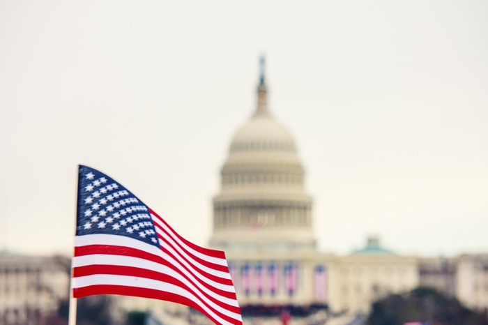 American flag being waved in front of the U.S. Capitol building