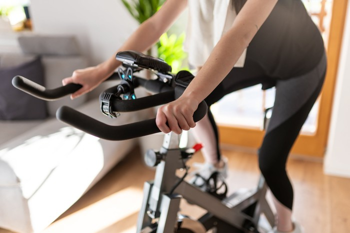 Women riding exercise bike.
