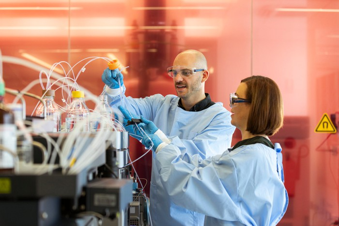 Two scientists operate a laboratory machine.