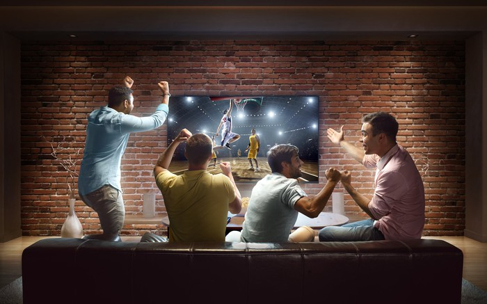 A group of excited friends watching a basketball game on large-screen TV mounted on a brick wall.