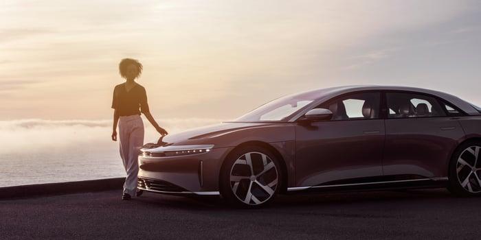 Woman standing by a Lucid Air sedan