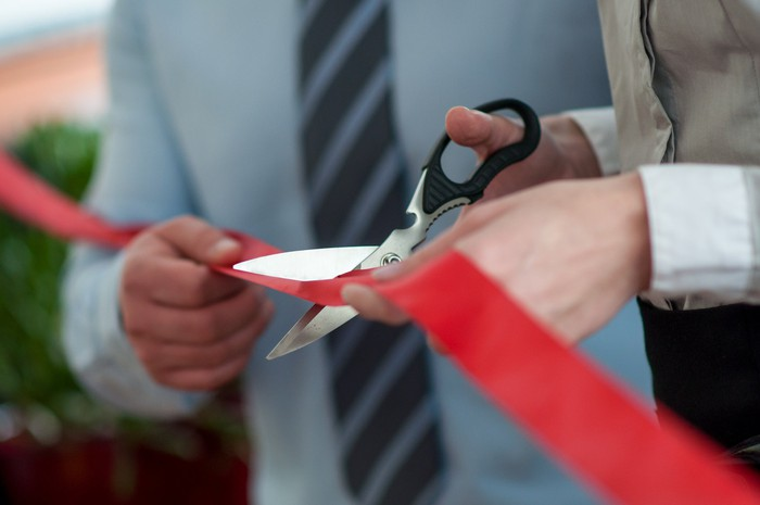 A ribbon cutting ceremony, representing the opening of a new restaurant.