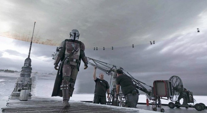 The Mandalorian walks across the StageCraft soundstage during production of the show.