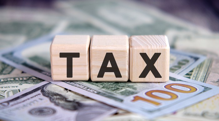 Tax - text on wooden cubes, on cash background.