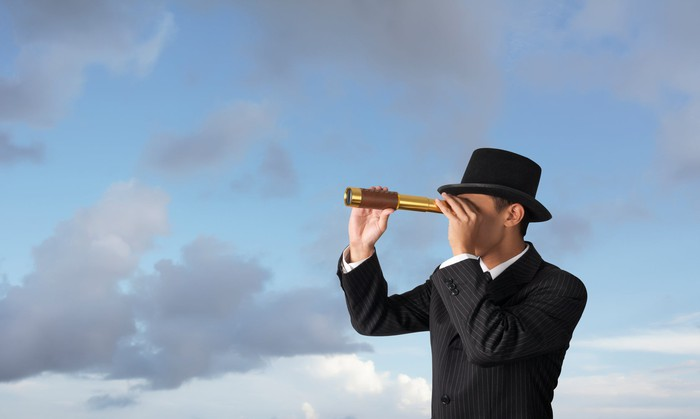 A businessman wearing a hat looks through a handheld telescope.