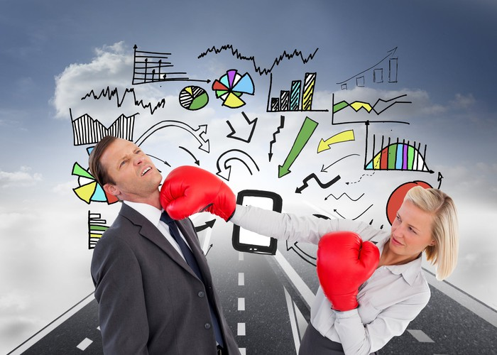 A businesswoman with boxing gloves landing a blow to a colleague with animated charts and graphs behind them.