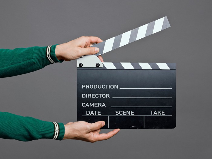 Person holding out a movie clapperboard.