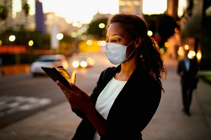 A woman wearing a mask and holding a mobile phone.