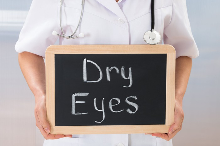 "A person with a stethoscope around their neck holding a small chalkboard with ""dry eyes"" written on it"