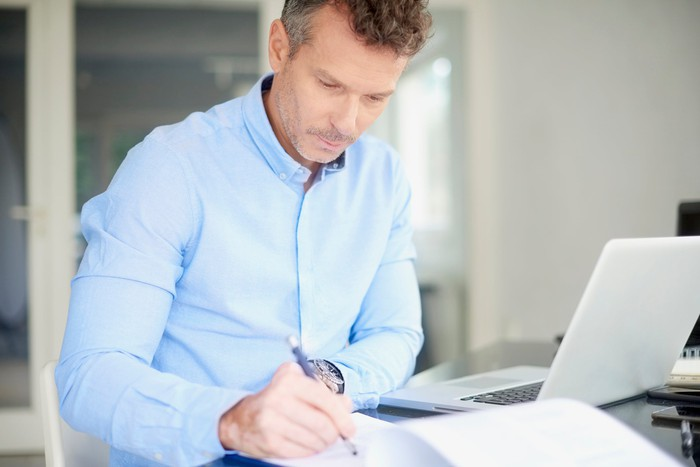 Man at laptop writing in notebook