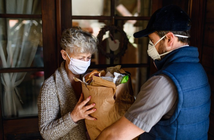 Man delivering groceries to woman, both donning facemasks.