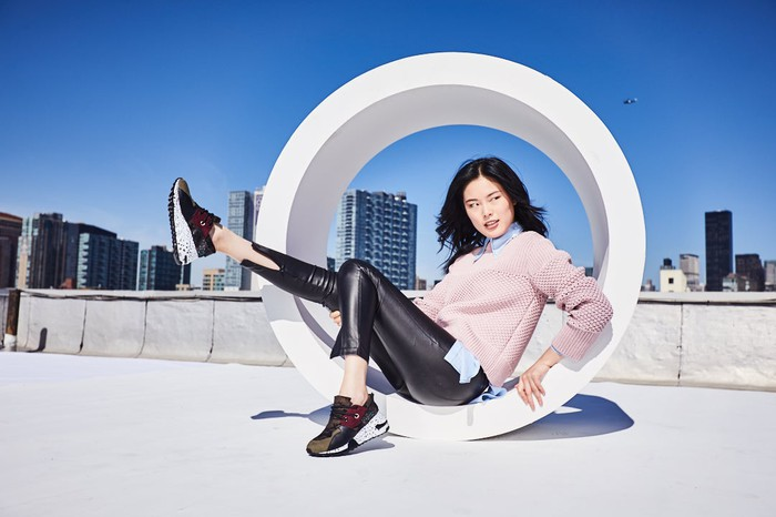 Woman sitting in a tube, showing off sneakers