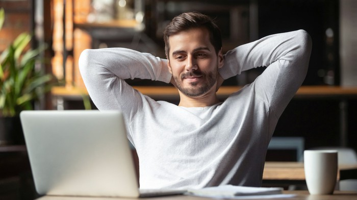 A relaxed man with his hands behind his head slightly smiling at a laptop.