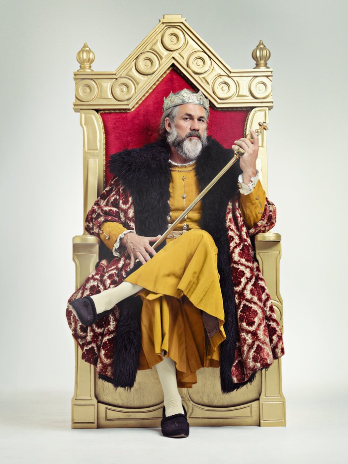 King in royal robes, sitting on gilded throne