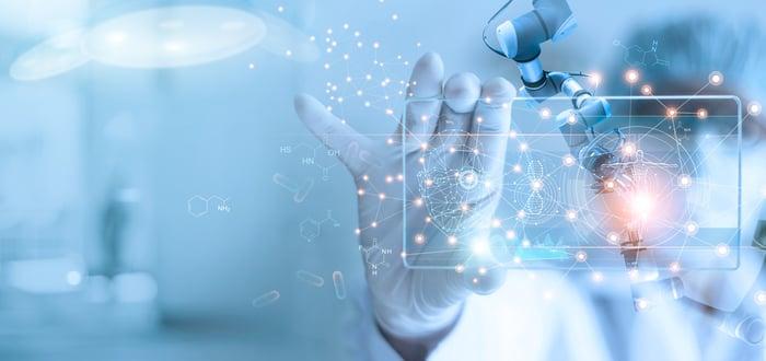 A medical researcher studies a transparent tablet.