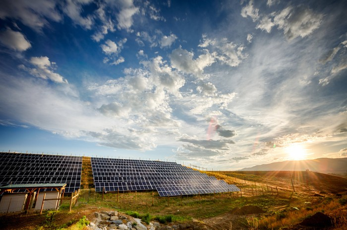 A solar farm with a bright sun in the background.