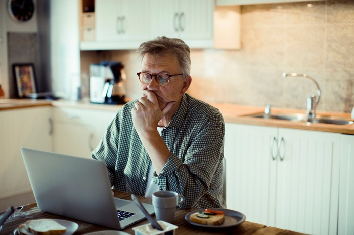 Older man sitting in the kitchen looking at a laptop