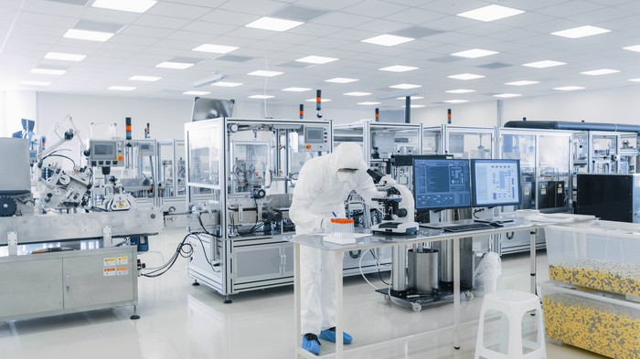 A high-tech research and development lab with machines, computers, and a worker in protective clothing.