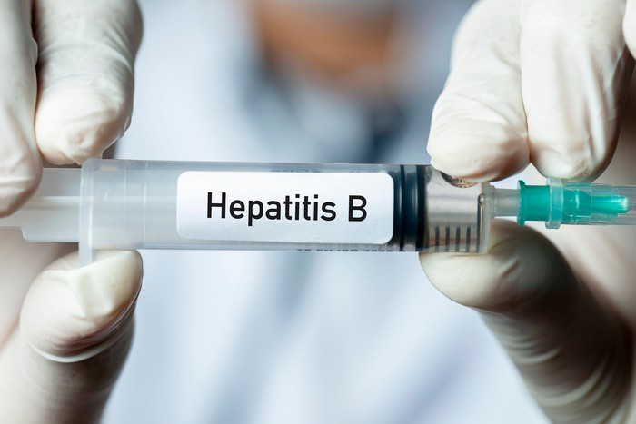 "Gloved hands holding a syringe with a ""hepatitis B"" label on it"