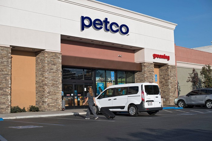 A Petco storefront with a minivan parked out front.