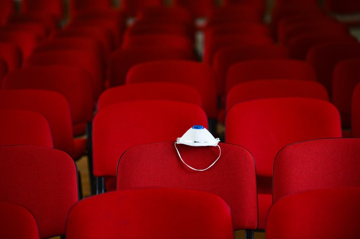 Empty seats in a movie theater with one having a mask on the back.