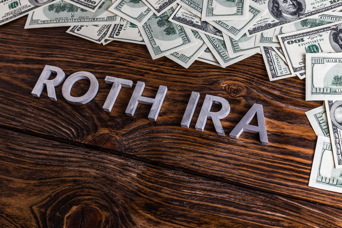 ROTH IRA laid on wooden surface with metal letters and U.S. dollar banknotes.