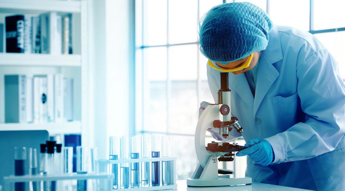 Researcher in lab coat looking at microscope, with vials nearby.