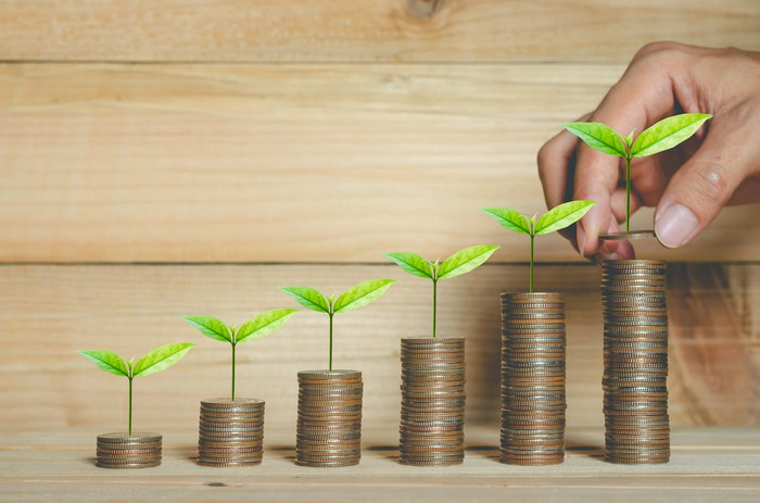 Stacks of coins with sprouts to represent ESG investing.
