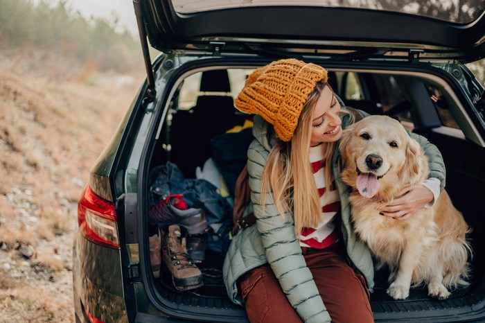 A young woman smiling sitting with her dog in the back of a car with a hatchback.