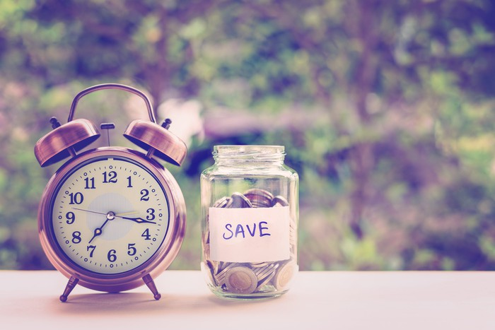 Analog clock next to jar with cash with