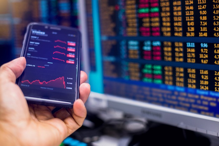 A smartphone with visible stock quotes being held next to a computer monitor showing real-time trade data.